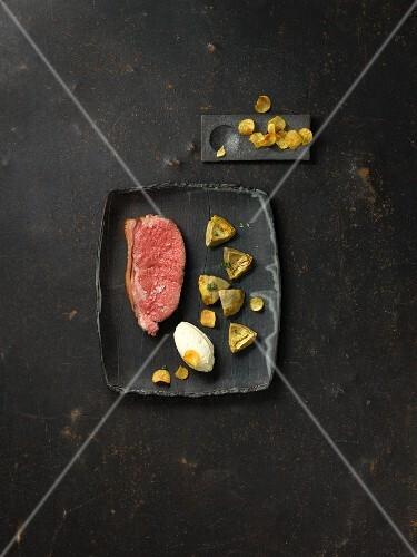 Aqua-aged beef with roasted artichoke hearts and potato ice cream