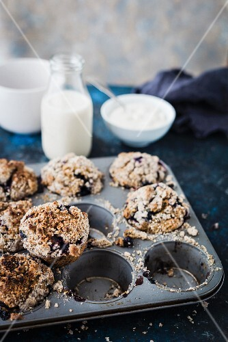 Blueberry crumble muffins with milk and yoghurt in the background