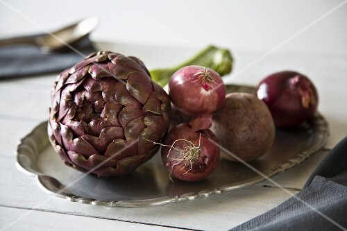 An arrangement of vegetables with an artichoke, onions and beetroot on the tray