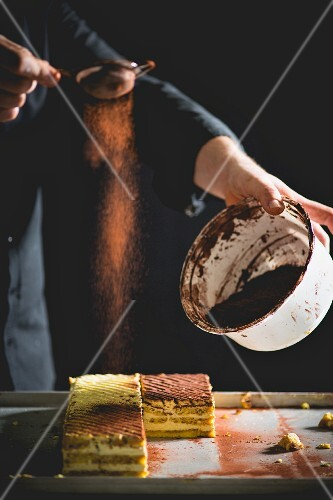 Tiramisu slices being dusted with cocoa