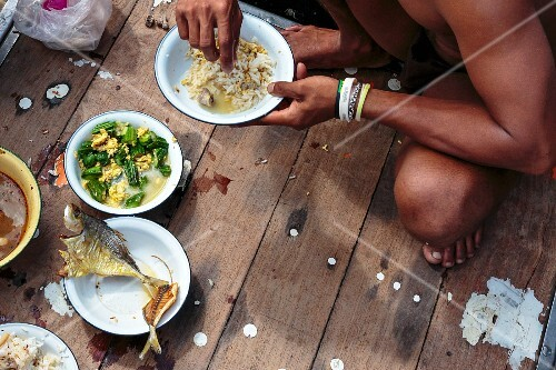 Burmese fishermen having breakfast on a Thai fishing boat, Phangnan, Thailand
