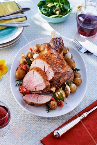 Roasted leg of lamb with potatoes, carved