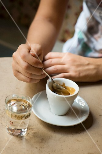 An espresso and a glass of water at the 'Orso Laboratorio Caffè' in Berthollet street, Turin, Italy