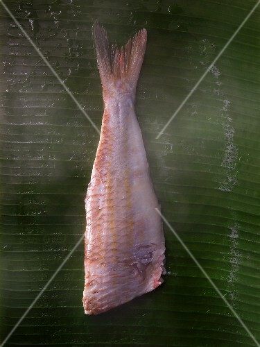A fish fillet being steamed on a banana leaf
