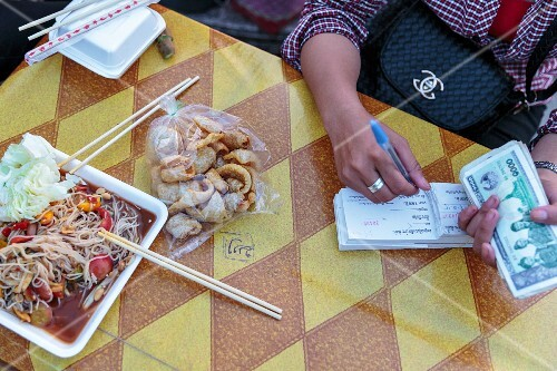 A woman at a market in Vientiane, Laos holding money and writing in a book next to portion of Som Tam with fermented rice noodles