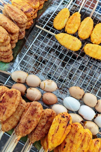 Sticky rice on skewers and eggs on a charcoal grill at a market in Vientiane, Laos