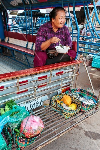 A woman sitting in a bus eating noodles