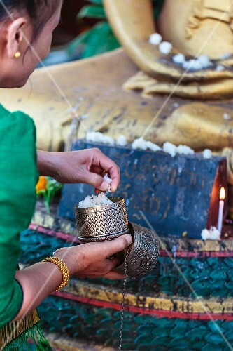 A woman placing cooked sticky rise in front of a Buddha statue