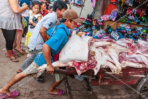 Men pushing a full barrow of fresh pork at a market in Vientiane, Laos