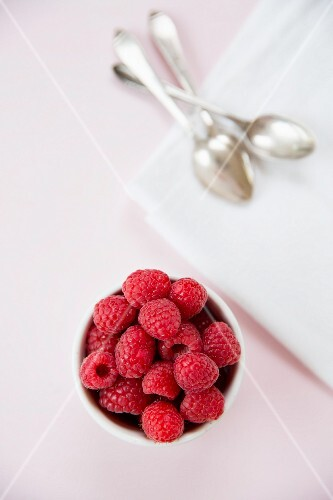 Raspberries in a white bowl on a pink tablecloth