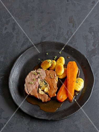 A slice of stuffed lamb's leg with carrots and potato gnocchi