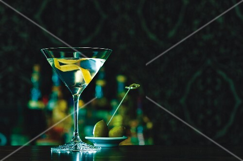 A martini in a glass with lemon zest with a green olive in the background