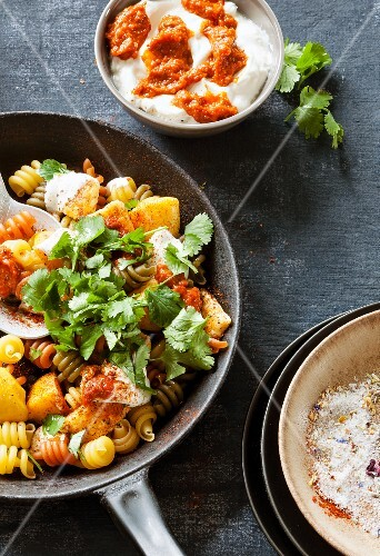 Colourful fried pasta with pumpkin and spicy harissa