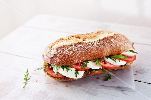 A baguette with mozzarella, tomato, pesto and rocket