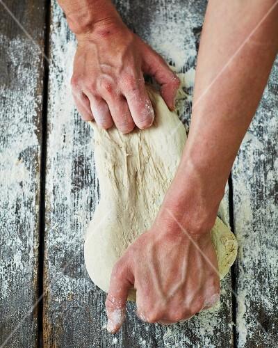 A baker kneading dough on a floured wooden surface