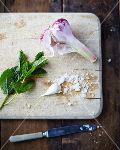 Garlic, sea salt and mint leaves on a wooden chopping board