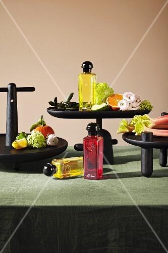 An arrangement of perfume bottles, fruit, flowers and vegetables