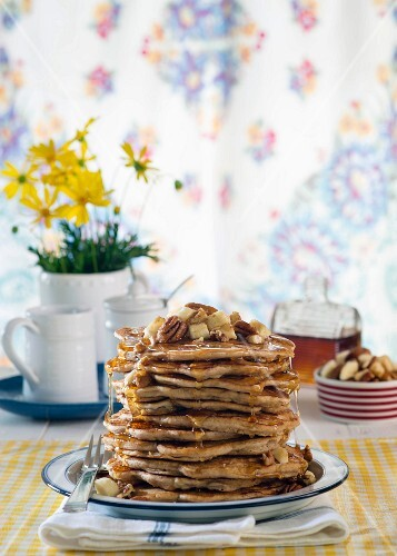 A stack of pancakes with banana and pecan nuts