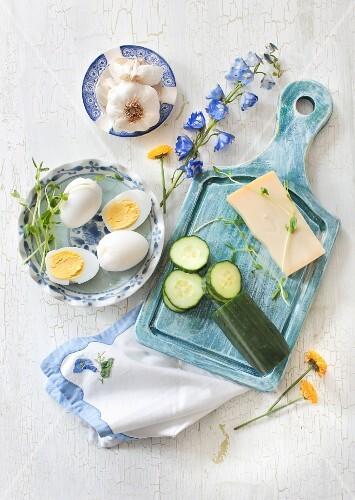 Ingredients for cheese and garlic salad: hard-boiled eggs, cucumbers, cheese and garlic