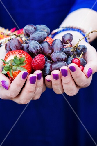 Hands holding fresh berries and grapes