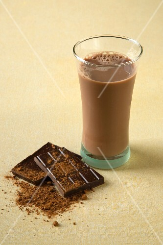 A glass of chocolate milk next to chocolate and cocoa powder