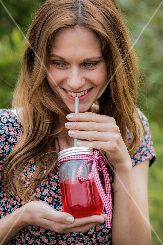 A woman drinking iced tea from a screw-top jar with a straw