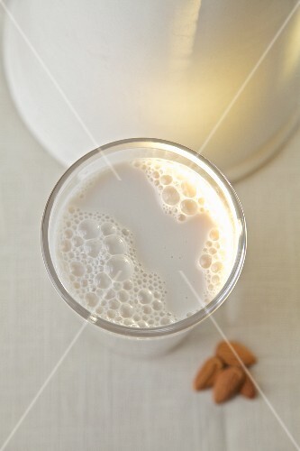 Almond milk in a glass in front of a white jug