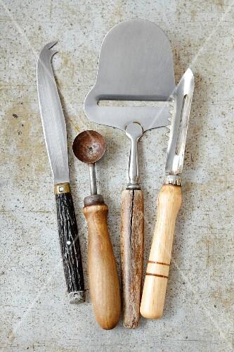 Vintage kitchen utensils: a cheese knife, a melon baller, a cheese cutter and a peeler