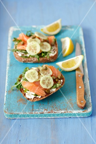 Wholemeal rolls topped with smoked salmon, cream cheese, cucumber and capers