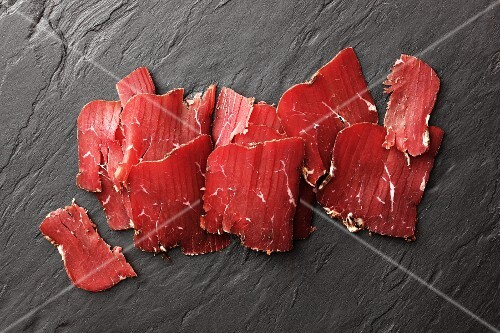 Sliced smoked beef on a slate surface (South Tyrol)