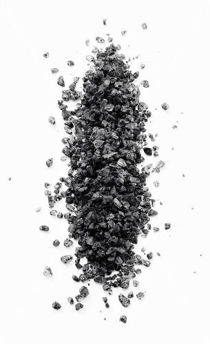 A pile of black vulcan salt on a black surface