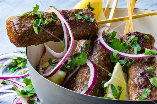Cevapcici on wooden skewers with onions, parsley and lemon in a grey bowl