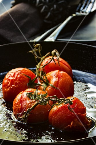 Oven-roasted tomatoes in a black iron pan with a fabric napkin and cutlery in the background