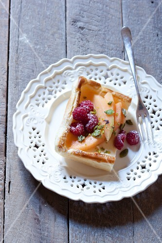 A slice of fruit cake with pears and raspberries