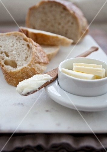 Sliced bread with butter and a wooden butter knife