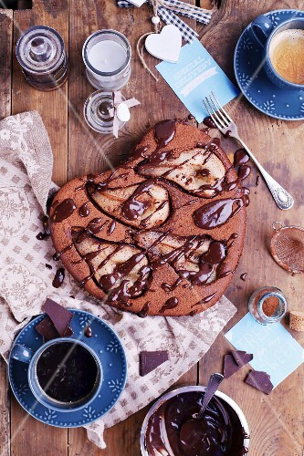 Pear and chocolate cake with coffee on a wooden table