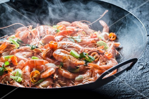 Steaming prawns with garlic, parsley and chilli peppers in a pan