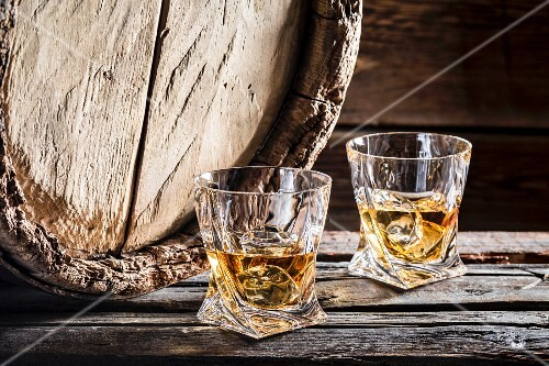Two glasses of whiskey on the rocks in front of an old wooden barrel