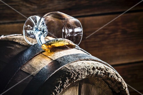 A overturned glass of cognac on an old wooden barrel