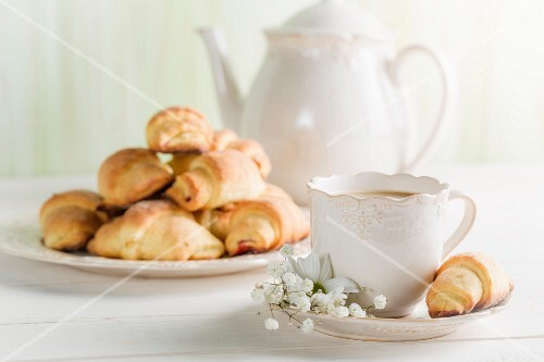 Coffee and croissants on a white table