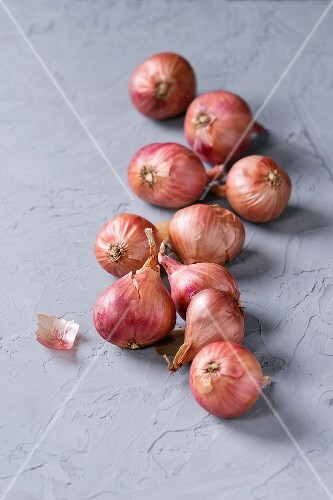 Small red onions on a grey textured surface