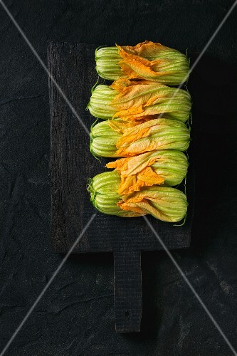 Courgette flowers on black chopping board