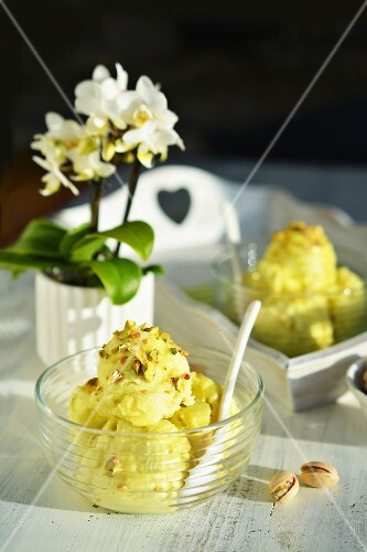 Pistachio ice cream in a glass bowl with flowers in the background