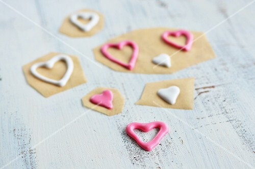 Piped sugar hearts on baking paper