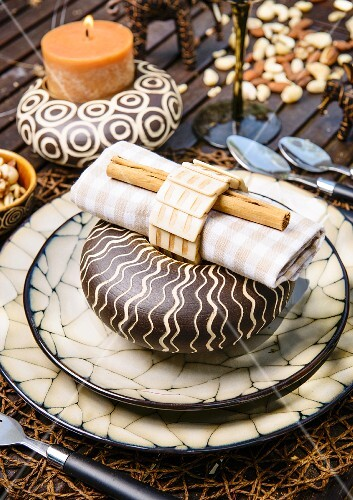 A Christmas place setting with elegant African decorations on a garden table