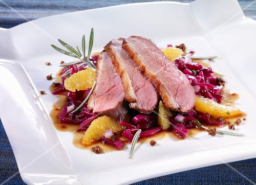 Duck breast on a bed of red cabbage with oranges