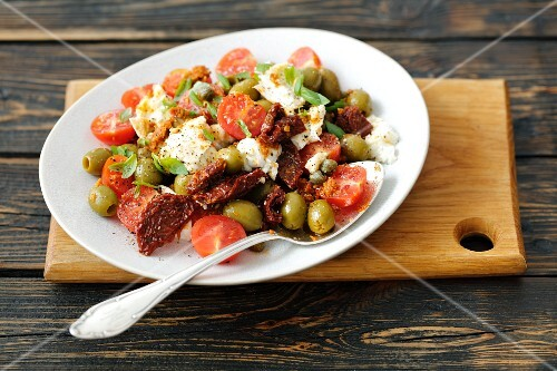 Salad with cherry tomatoes, dried tomatoes, mozzarella, olives and basil