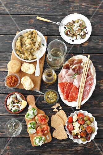 A selection of antipasti (artichokes, arancini, a cold cuts platter, courgette, pesto, bruschetta, seafood salad, tomato and mozzarella salad, Italy)