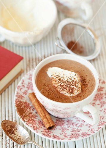 A cup of cinnamon hot chocolate made with almond milk and topped with cream