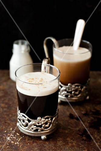 Black coffee with coconut liqueur and cream in vintage glasses